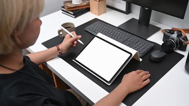Toma recortada de mujer creativa trabajando en tableta digital mientras está sentado en la oficina moderna.