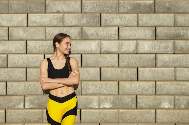 Toma recortada de mujer joven hermosa positiva con ropa deportiva negra y amarilla de moda que descansa al aire libre, posando contra la pared de ladrillo en blanco con espacio de copia para su contenido