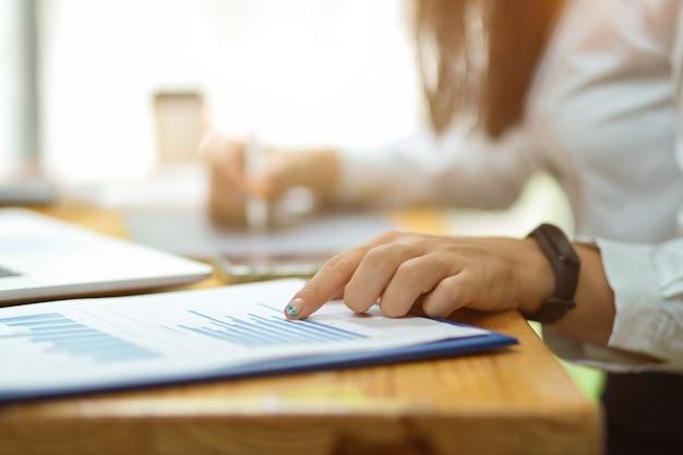 Toma recortada de mujer señalando con el dedo sobre documentos financieros con borrosa en el fondo