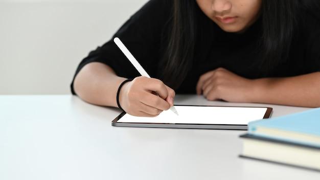 Toma recortada de niña haciendo sus deberes con tableta digital. educación en línea e-learning.