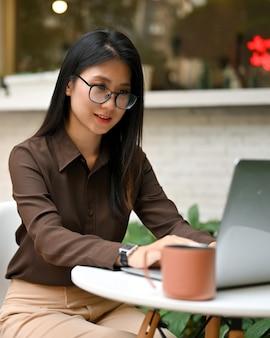 Toma recortada de oficinista con anteojos trabajando con ordenador portátil en mesa redonda en café