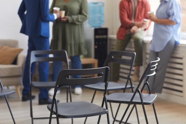Toma recortada de sillas vacías en círculo durante la reunión del grupo de apoyo con gente charlando en la superficie, espacio de copia