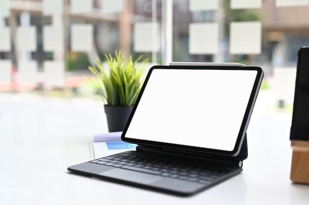 Toma recortada de tableta con teclado inteligente en mesa blanca. pantalla en blanco para montaje de visualización de gráficos.