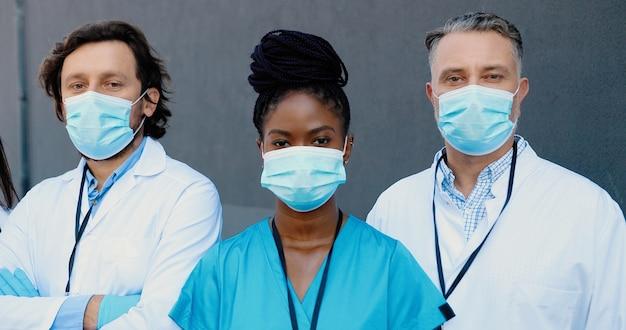 Toma de retrato de hombres y mujeres jóvenes de raza mixta médicos con máscaras médicas y batas blancas de pie y mirando a la cámara. médicos multiétnicos, hombres y mujeres. concepto de coronavirus.