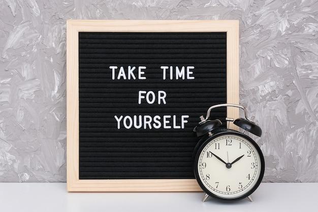 Toma tiempo para ti mismo. cita motivacional en pizarra y despertador negro sobre mesa.
