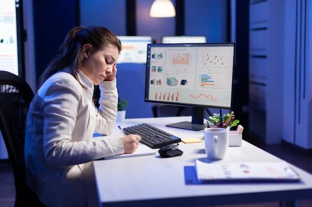 Toma trasera de una mujer abrumada que trabaja de noche frente a la computadora, escribiendo notas en los informes anuales del cuaderno, verificando el plazo financiero
