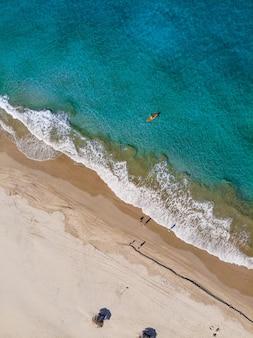 Toma vertical aérea de personas en la orilla de la playa durante el día