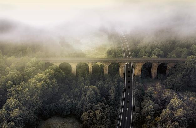 Toma de vista aérea de una carretera rodeada de vegetación y nubes