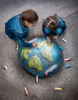 Toma de vista superior de dos niñas dibujando una imagen realista de la tierra con tizas en el suelo