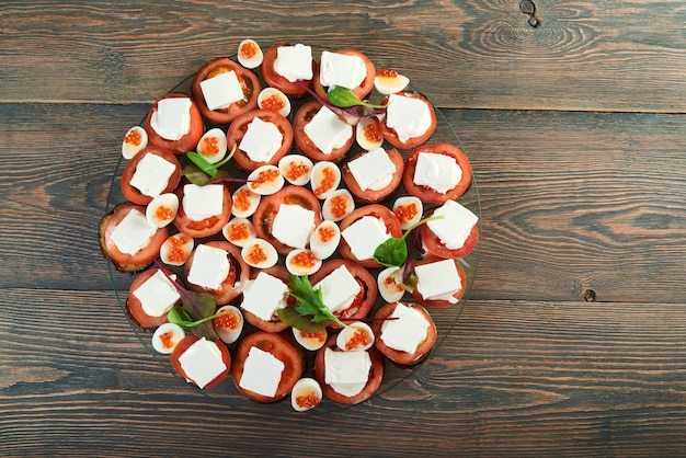 Toma de vista superior de mezcla de vegetales en un plato con queso y huevos duros decorados con caviar berenjena tomates verduras comida saludable dieta mesa de restaurante gourmet delicioso.