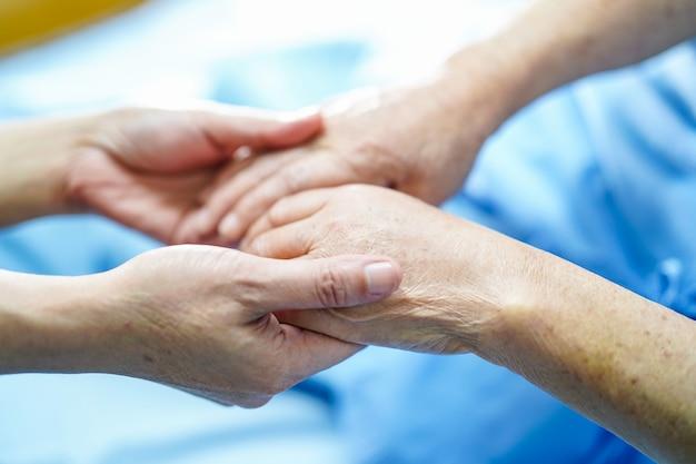 Tomados de la mano asiática anciana anciana paciente con amor, cuidado, ánimo y empatía.