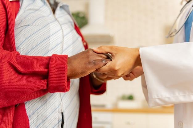 Tomados de la mano. cerca de la enfermera en la chaqueta blanca tomados de la mano del paciente de piel oscura