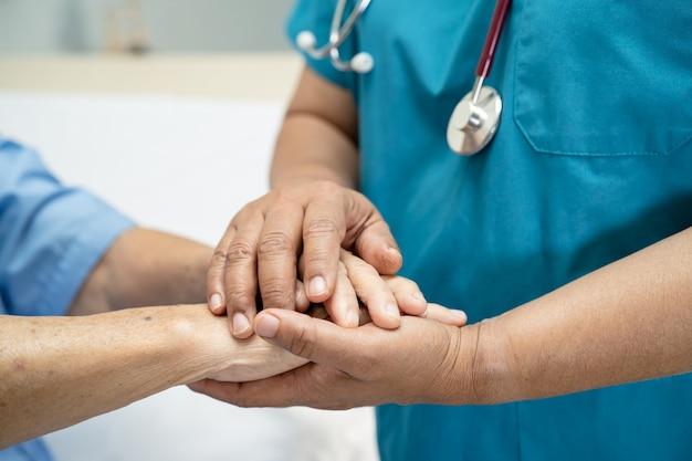 Tomados de la mano paciente asiático mayor o anciana con amor, cuidado, aliento y empatía en la enfermería
