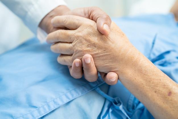 Tomados de la mano paciente mayor asiático de la mujer con amor.
