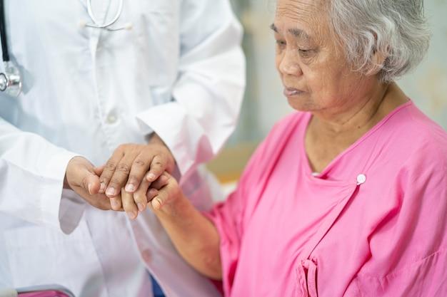 Tomados de la mano paciente mujer mayor asiática con amor.
