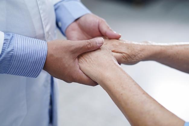 Tomados de la mano paciente senior mujer asiática con amor y cuidado.