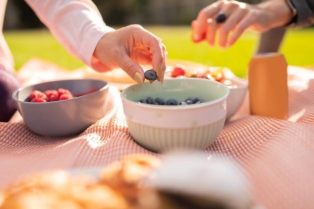 Tomando arándanos. cerca de mujer tomando arándanos mientras almuerza afuera con un amigo