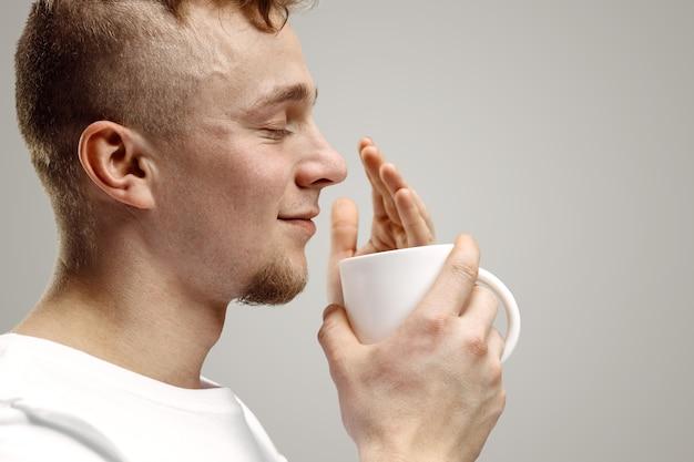 Tomando un café. apuesto joven sosteniendo la taza de café, sonriendo mientras está de pie contra la pared gris
