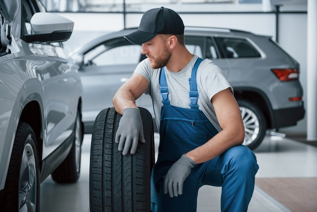 Tomando un descanso. mecánico sosteniendo un neumático en el taller de reparación. reemplazo de neumáticos de invierno y verano.