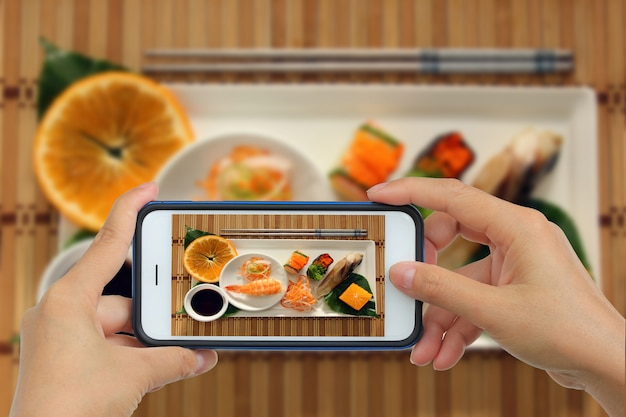 Tomando foto de sushi con smartphone.
