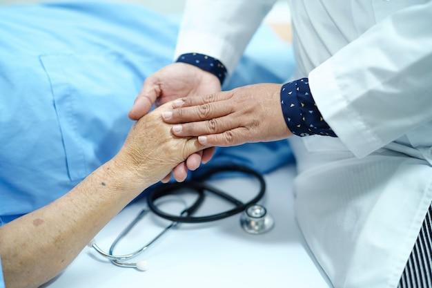 Tomando de la mano a una paciente anciana o anciana asiática con amor, cuidado, estímulo y empatía