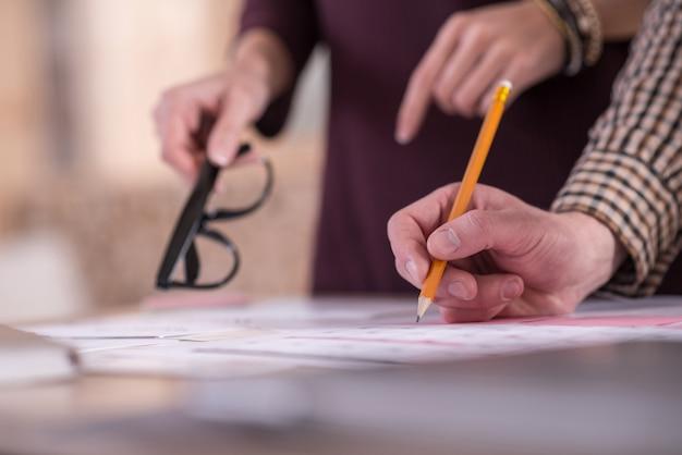 Tomando notas. cerca de un lápiz en manos de un hombre agradable agradable mientras toma notas