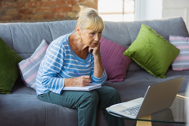 Tomando notas durante la lección senior mujer estudiando en casa obteniendo cursos en línea