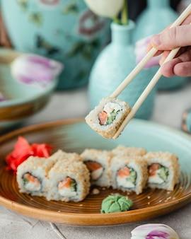 Tomando rollos de sushi con palillos.