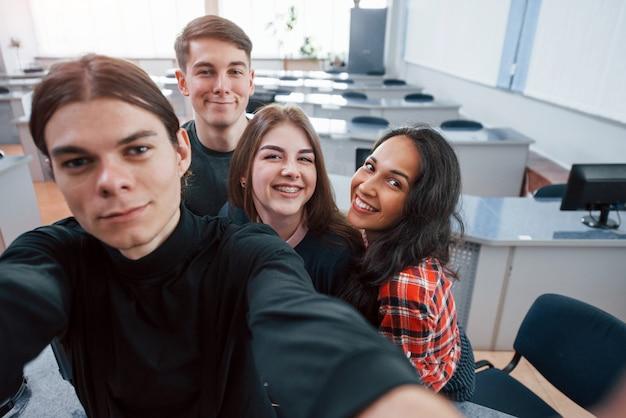 Tomando una selfie. grupo de jóvenes en ropa casual que trabajan en la oficina moderna