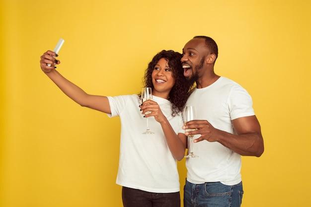 Tomando selfie juntos. celebración del día de san valentín, feliz pareja afroamericana aislada sobre fondo amarillo. concepto de emociones humanas, expresión facial, amor, relaciones, vacaciones románticas.