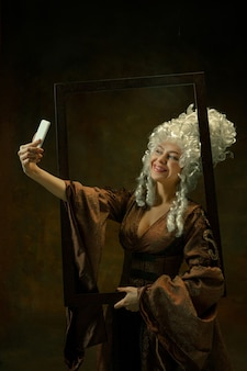 Tomando selfie. retrato de mujer joven medieval en ropa vintage con marco de madera sobre fondo oscuro. modelo femenino como duquesa, persona real. concepto de comparación de épocas, moda, belleza.