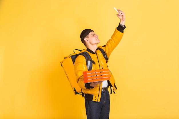 Tomando selfie, vlog. emociones del repartidor caucásico en amarillo