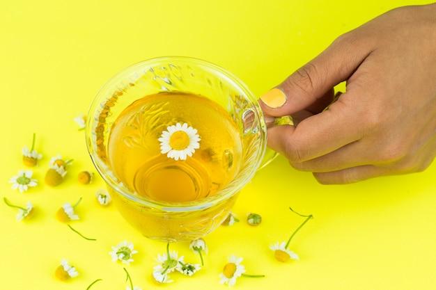 Tomando una taza de té de manzanilla aislado en fondo amarillo