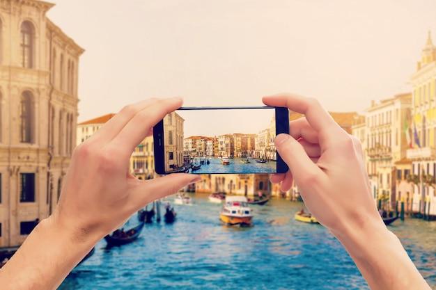 Tomar fotografías en un teléfono inteligente móvil en góndola en canal grande