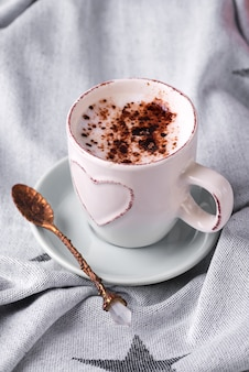 Tomar una taza de café con chocolate sobre una manta en la cama