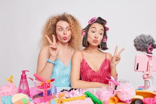 Las tomas en interiores de mujeres blogueras de raza mixta hacen grabaciones de gestos de paz que transmiten en vivo videos sobre contenido cosmético rodeados de productos de belleza que brindan recomendaciones sobre cómo maquillarse.