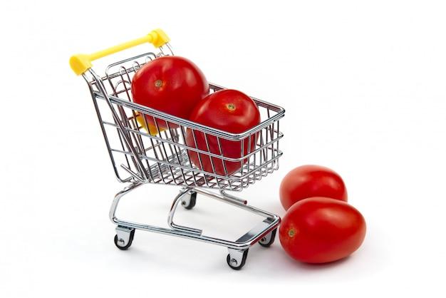 Un tomate en el carrito de compras aislado sobre fondo blanco. sabrosos tomates rojos maduros en carrito de compras. concepto comercial de tomate. concepto de compra en línea. carro y tomate sobre un fondo blanco.
