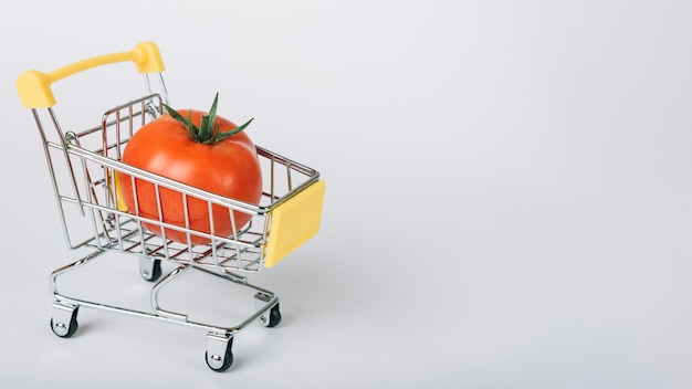 Tomate en carrito de compras en superficie blanca