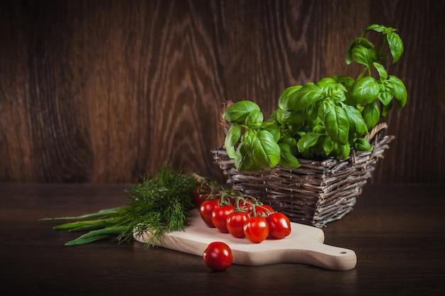 Tomate cherry y hierbas frescas verdes sobre madera
