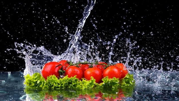 Tomate fresco cereza y ensalada fresca verde con salpicaduras de gota de agua. macro gotas de agua caen sobre los tomates cherry rojos y hacen salpicaduras