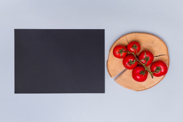 Tomate fresco rojo en tocón de árbol cerca del estado negro sobre fondo gris