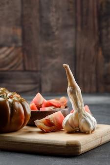 Tomate kumato con rodajas en placa, vista lateral de ajo en pared de azulejos grises y piedra