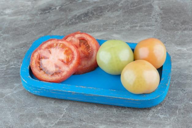 Tomate maduro cortado a la mitad con tomates verdes inmaduros en placa de madera azul.