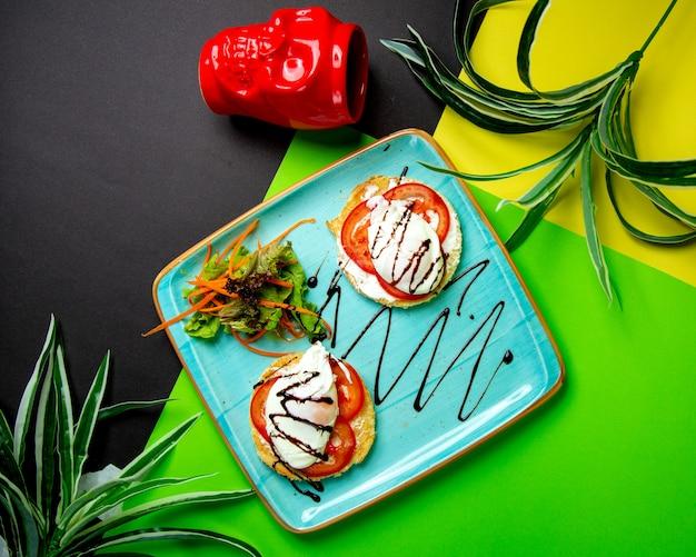 Tomate y mozzarella sobre tostadas redondas servidas con ensalada verde