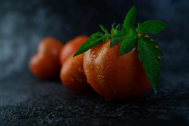 Tomate orgánico con gotas de agua en primer plano macro.