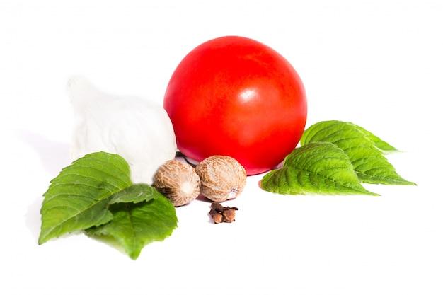 Tomate con pimienta y ajo en el fondo blanco, composición de tomates y opinión superior de las especias