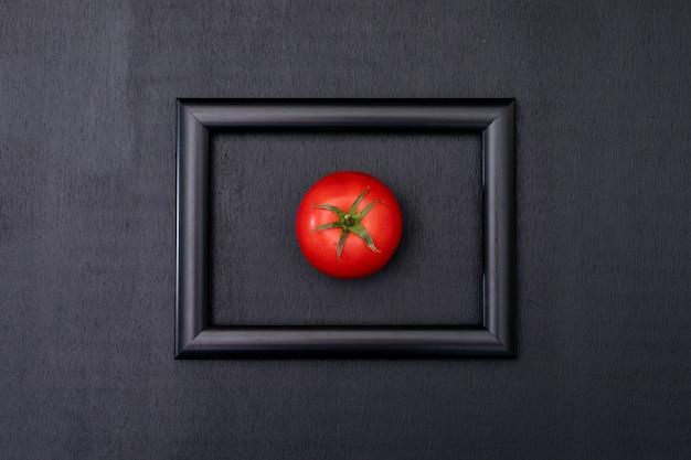 Tomate rojo brillante fresco en el centro del marco negro en la vista superior de la superficie negra