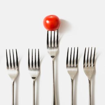 Tomate rojo cereza en tenedor contra el fondo blanco