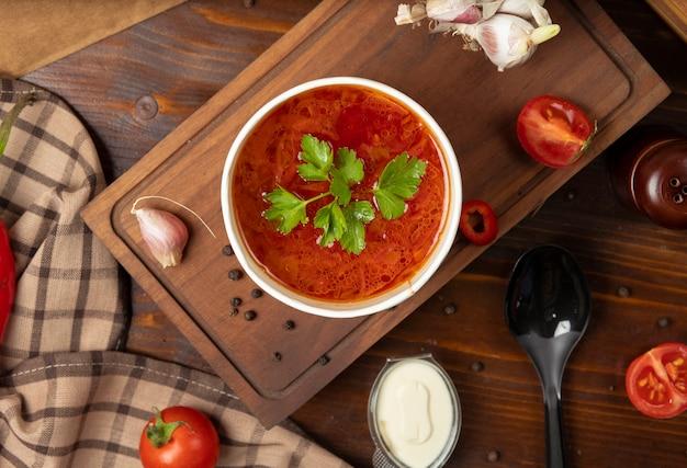 Tomate rojo, sopa de verduras borsh en un tazón de taza desechable servido con verduras verdes