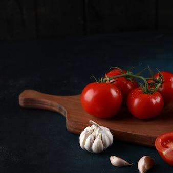 Tomates y ajos sobre un fondo azul.